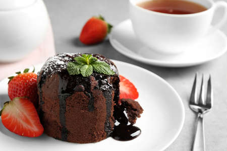Delicious warm chocolate lava cake with mint and strawberries on table, closeup
