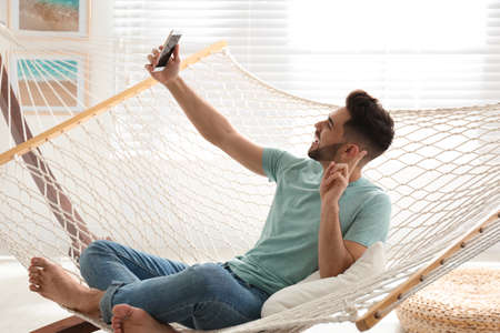 Young man taking selfie in hammock at home