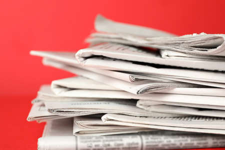 Stack of newspapers on red background, closeup. Journalist's work