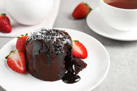 Delicious warm chocolate lava cake with mint and strawberries on table. Space for text