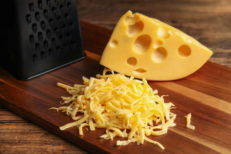 Tasty grated and whole cheese on wooden table Stock fotó