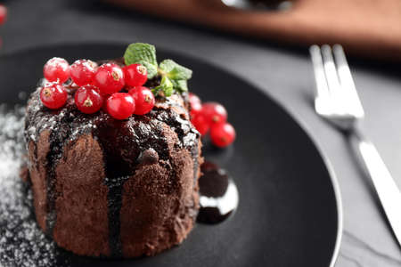 Delicious warm chocolate lava cake with mint and berries on table, closeup. Space for text