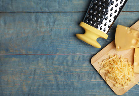 Tasty grated cheese on blue wooden table, flat lay. Space for text