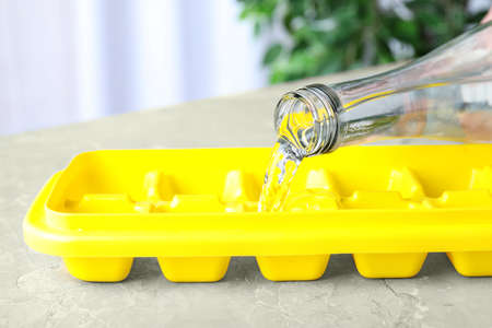 Pouring water into ice cube tray on table, closeup Imagens