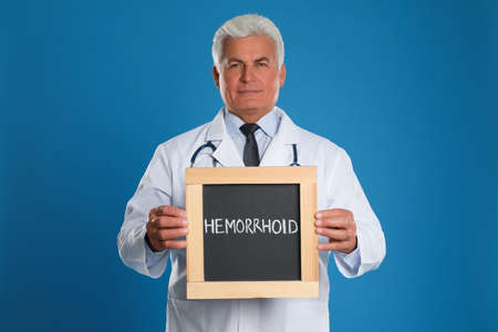 Doctor holding blackboard with word HEMORRHOID on blue background