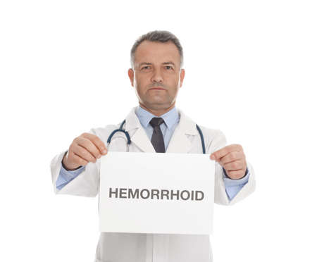 Doctor holding sign with word HEMORRHOID on white background