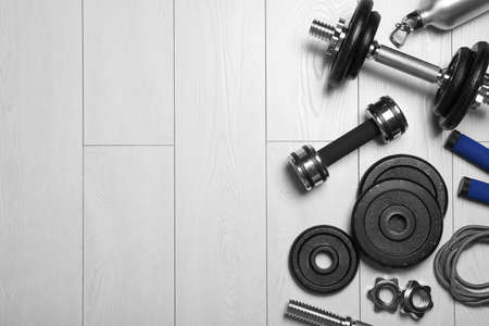 Gym equipment on wooden floor, flat lay. Space for text Stok Fotoğraf