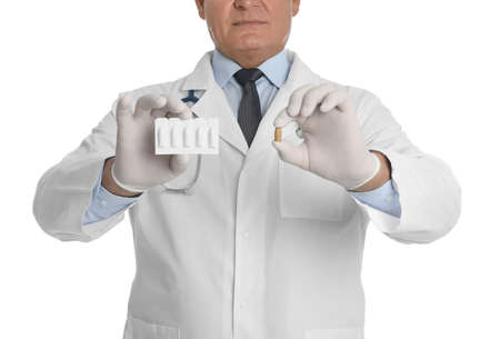 Doctor holding suppositories for hemorrhoid treatment on white background, closeup