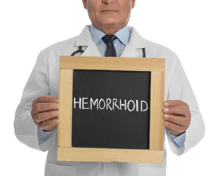 Doctor holding blackboard with word HEMORRHOID on white background, closeup