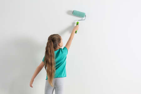 Little child painting with roller brush on white wall indoors. Space for text