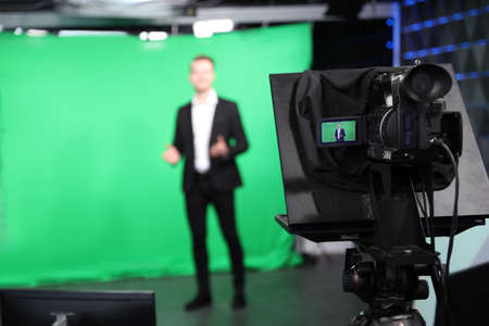 Presenter working in studio, focus on video camera