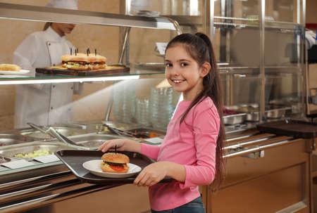 Kleines Mädchen mit Plastiktablett und Burger in der Nähe der Servierlinie in der Kantine. Schulessen