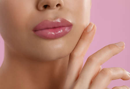Young woman with beautiful full lips on pink background, closeup