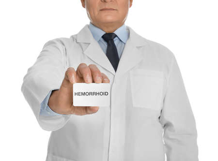 Doctor holding business card with word HEMORRHOID on white background, closeup