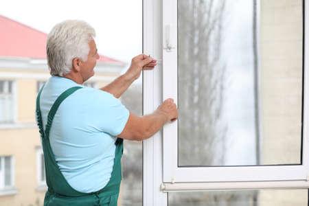 Volwassen bouwvakker die plastic raam binnenshuis repareert