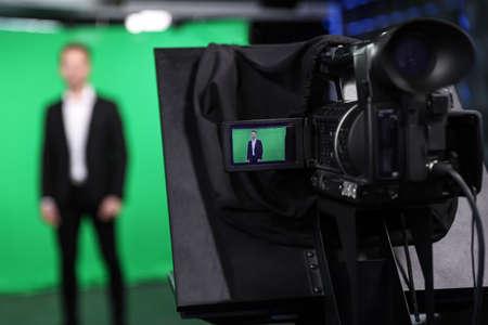 Presentador trabajando en estudio, foco en la pantalla de la cámara de video