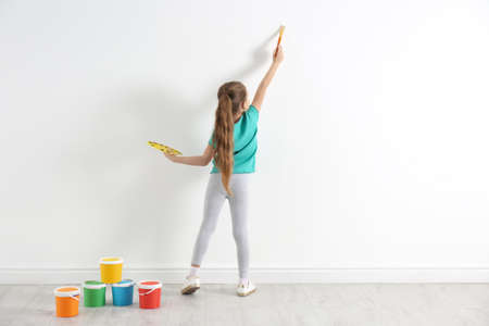 Little child painting on white wall indoors