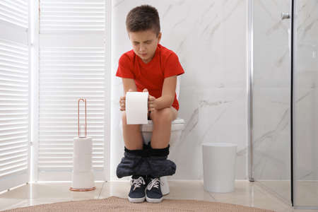 Boy with paper suffering from hemorrhoid on toilet bowl in rest room Reklamní fotografie
