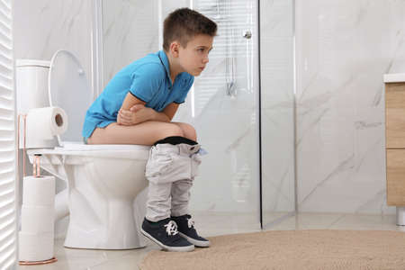 Boy suffering from hemorrhoid on toilet bowl in rest room
