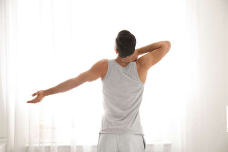 Man stretching near window at home. Lazy morning