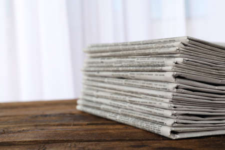 Stack of newspapers on wooden table, space for text. Journalist's work
