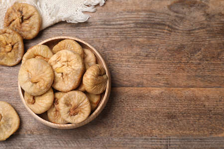 Tasty dried figs in bowl on wooden table, top view. Space for text