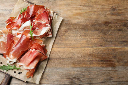 Pile of tasty prosciutto on wooden table, top view. Space for text