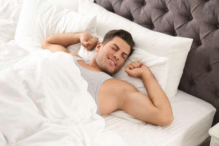 Man awakening on bed at home. Lazy morning