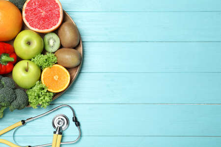 Fruits, vegetables and stethoscope on light blue wooden background, flat lay with space for text. Visiting nutritionist