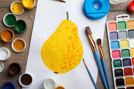 Flat lay composition with childs painting of pear on wooden table Banco de Imagens