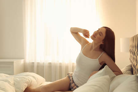 Young woman stretching on bed at home. Lazy morning