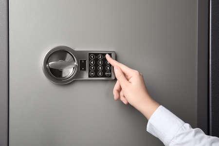 Vrouw die stalen kluis opent met elektronisch slot, close-up