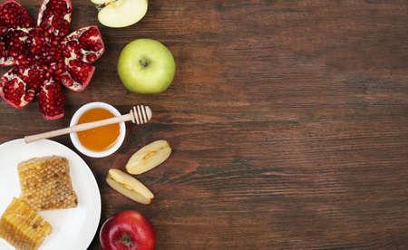 Composición laicos plana con miel y frutas en la mesa de madera, espacio para texto. Fiesta de Rosh Hashaná