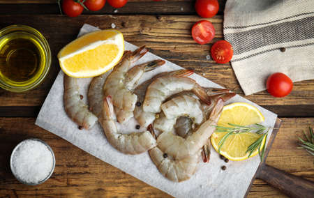 Flat lay composition with fresh raw shrimps on wooden table