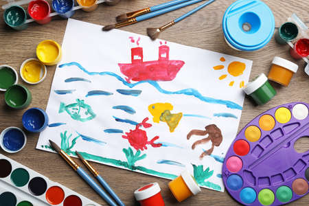 Flat lay composition with childs painting of underwater life on wooden table Banco de Imagens