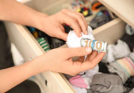 Frau versteckt Geld in Socke, Nahaufnahme. Finanzielle Einsparungen
