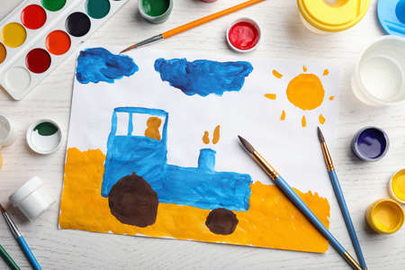 Flat lay composition with childs painting of tractor on white wooden table