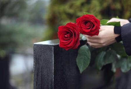 Frau mit roten Rosen in der Nähe von Grabstein aus schwarzem Granit im Freien, Nahaufnahme. Begräbniszeremonie Standard-Bild