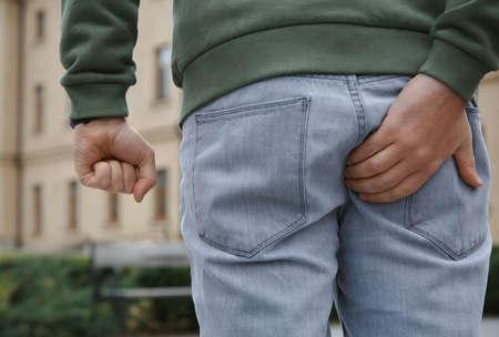 Man suffering from hemorrhoid pain outdoors, back view Zdjęcie Seryjne