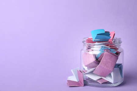 Frasco de vidrio lleno de hojas de papel dobladas sobre fondo violeta, espacio para texto