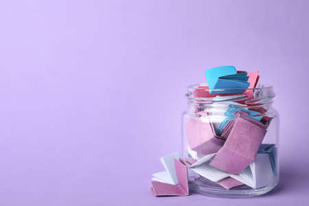 Glass jar full of folded paper sheets on violet background, space for text