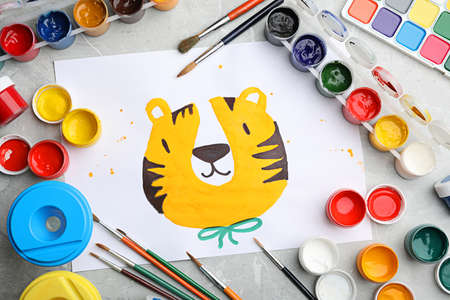 Flat lay composition with childs painting of tiger on marble table