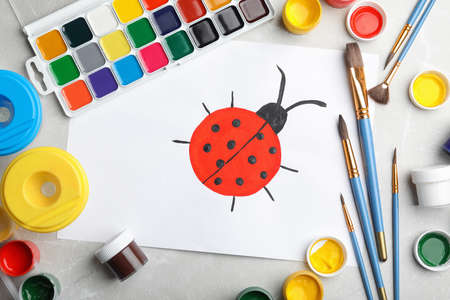 Flat lay composition with childs painting of ladybug on marble table