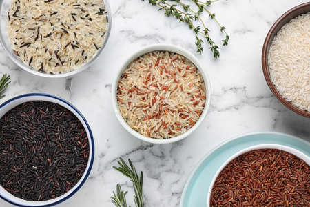Flat lay composition with brown rice on marble table Stock Photo