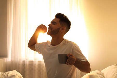 Young man with cup of coffee on bed at home. Lazy morning Stok Fotoğraf