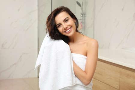 Junge Frau trocknet Haare mit Handtuch im Badezimmer Standard-Bild