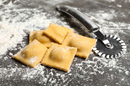 Ravioli and cutter on grey table, closeup. Italian pasta Reklamní fotografie