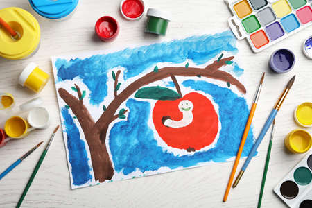 Flat lay composition with childs painting of apple tree with worm on white wooden table