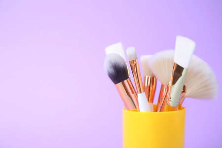 Set of professional makeup brushes in holder on lilac background. Space for text