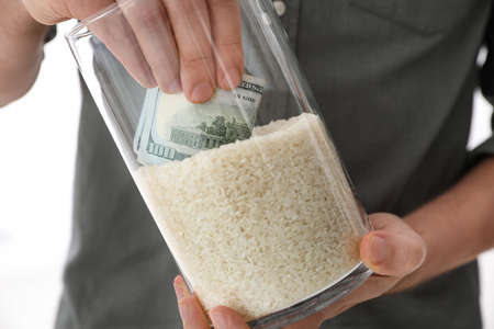Man hiding money in jar of rice indoors, closeup. Financial savings